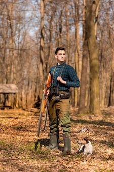 Jesienny sezon polowań. mężczyzna myśliwy z pistoletu odrobiną swojego psa. polowanie w lesie