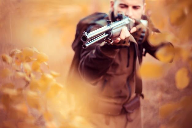 Jesienny sezon polowań myśliwy celujący karabin w leśnej lufie pistoletu