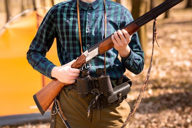 Jesienny sezon polowań. myśliwy mężczyzna z pistoletem. polowanie w lesie