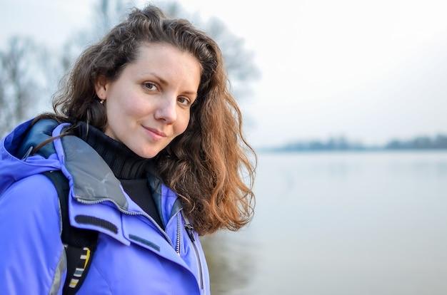 Jesienny spacer nad jeziorem. młoda kobieta idzie jesienią nad brzegiem rzeki.