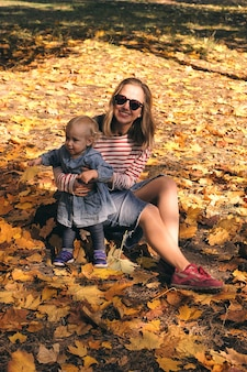 Jesienny spacer rodzinny w lesie. piękny park z suchymi żółtymi i czerwonymi liśćmi. kochająca matka przytula córkę.