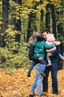 Jesienny spacer rodzinny w lesie. piękny park z suchymi żółtymi i czerwonymi liśćmi. matka z córką i ojcem z synem i ojcem trzymając się za ręce.