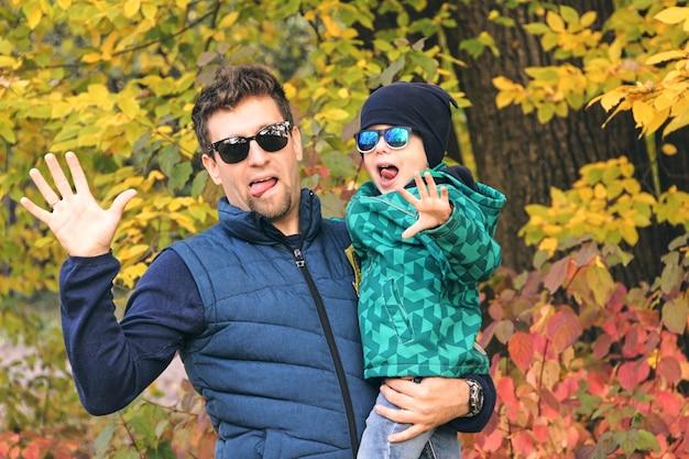 Jesienny spacer rodzinny w lesie. piękny park z suchymi żółtymi liśćmi. syn i ojciec trzymający się za ręce.
