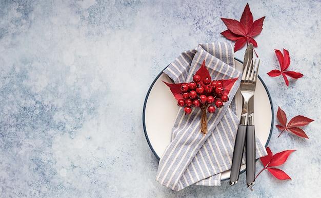 Jesienny stół z czerwonymi jesiennymi liśćmi, czerwonymi ozdobnymi jagodami, widelcem i nożem