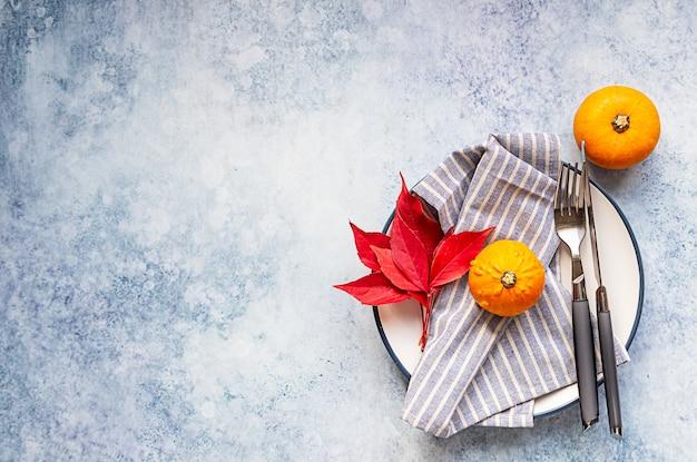 Jesienny stół z mini dekoracyjnymi dyniami, jesiennymi czerwonymi liśćmi, widelcem i nożem