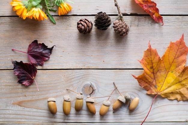Jesienny stół z suchymi liśćmi, szyszkami, żołędziami