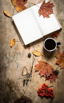 Jesienny styl. otwórz książkę przy filiżance gorącej kawy. na drewnianym tle.