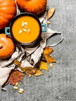 Jesienny styl. zupa dyniowa z dojrzałej dyni na kamiennym stole.
