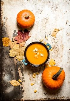 Jesienny styl. zupa dyniowa z pestkami. na tle rustykalnym.
