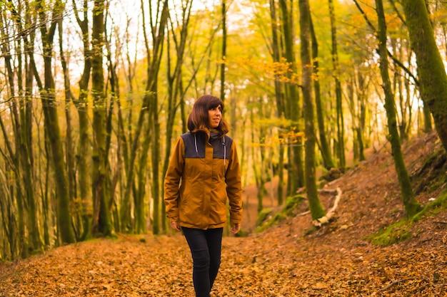 Jesienny styl życia, młoda kobieta w żółtej kurtce w lesie pełnym drzew. las artikutza w san sebastin, gipuzkoa, kraj basków. hiszpania