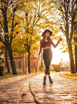 Jesienny styl życia o zachodzie słońca blondynka kaukaska kobieta w czerwonym swetrze i czarnym kapeluszu ciesząca się przyrodą w parku z drzewami spacerując piękną ścieżką parku miejskiego