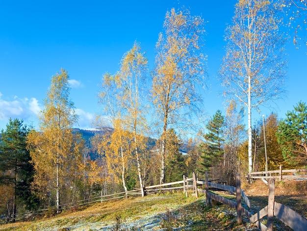 Jesienny szron na polanie na obrzeżach górskiej wioski