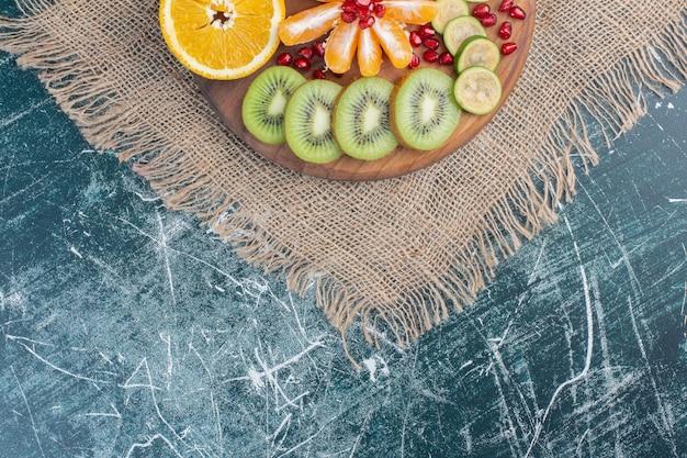 Jesienny talerz owoców na białym tle na niebieskiej powierzchni.