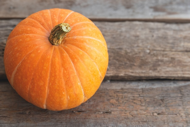 Jesienny tło. naturalna jesień widok dyni na drewniane tła. inspirująca tapeta z października lub września. zmiana pór roku koncepcja dojrzałej żywności ekologicznej. halloween party święto dziękczynienia