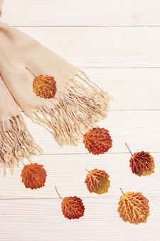 Jesienny wiatr od muchy beżowy szalik i naturalne czerwone liście osiki, jesień, koncepcja jesieni.