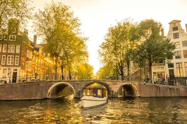 Jesienny wieczór na kanale amsterdamskim. łódź wypłynie spod mostu. typowe domy i wiele rowerów na nabrzeżu