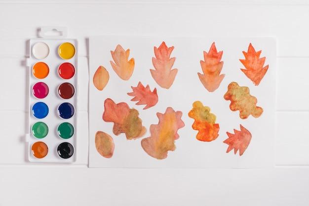 Jesienny wieniec krok po kroku. krok 1: maluj jesienne liście różnymi kształtami i kolorami akwarelami. widok z góry