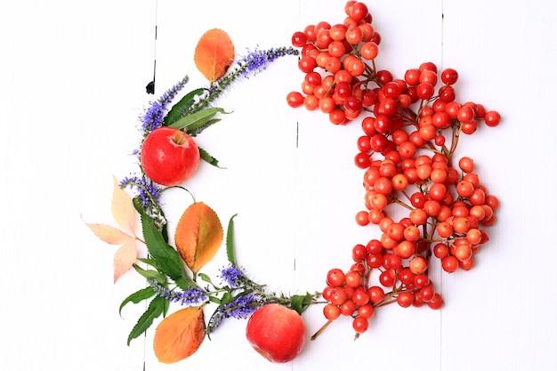 Jesienny wieniec ozdobiony jagodami, owocami, liśćmi i kwiatami na białym drewnianym tle widok z góry