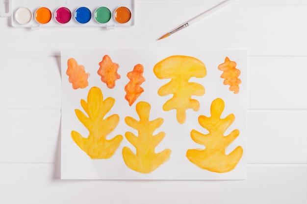 Jesienny wieniec z papieru krok po kroku. krok 1: pomaluj jesienne liście o różnych kształtach, rozmiarach i kolorach akwarelami. widok z góry