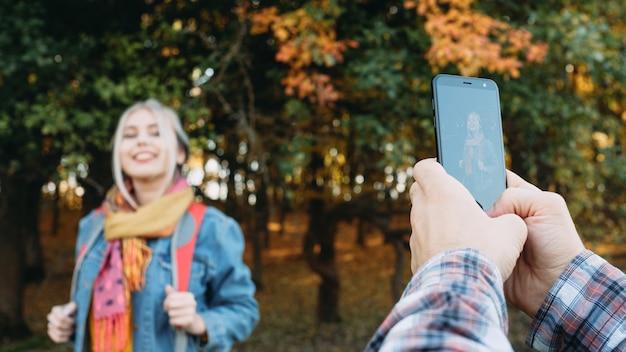 Jesienny wypoczynek para korzystających z czasu w parku przyrody, robienie zdjęć na smartfonie