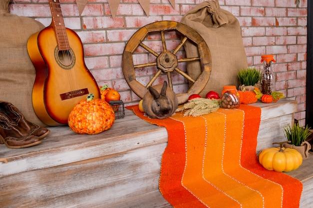 Jesienny wystrój z żyta, pszenicy, z żółtymi liśćmi klonu, dyniami, czerwonymi jabłkami. drewno postarzane. oferty sezonowe i świąteczna kartka pocztowa. jesienna dekoracja.