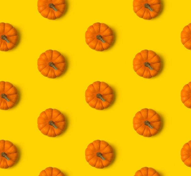 Jesienny wzór. dynie na żółtym stole