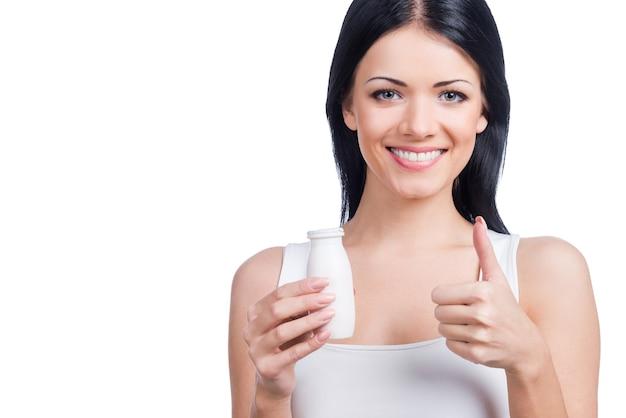 Jeśli chcesz być zdrowy, wybierz to! piękna młoda uśmiechnięta kobieta trzyma butelkę i gestykuluje stojąc na białym tle