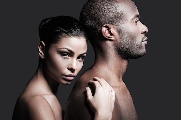Jest absolutnie mój. piękna kobieta rasy kaukaskiej przywiązująca się do pleców przystojnego afrykańskiego mężczyzny i patrząca w kamerę, stojąc na szarym tle