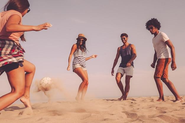Jest naprawdę dobra w piłce nożnej. grupa wesołych młodych ludzi bawiących się piłką nożną na plaży