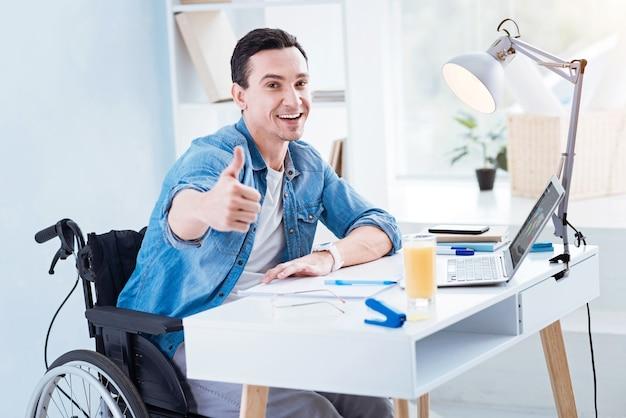 Jest ok. wesoły niepełnosprawny mężczyzna utrzymujący uśmiech na twarzy i podnoszący kciuk do góry