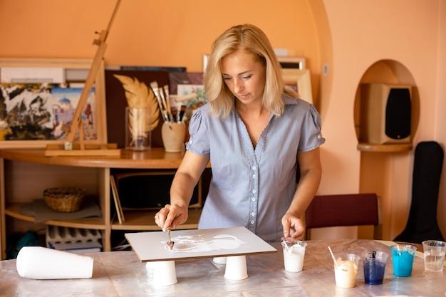 Jest praca w pracowni artysty, piękna kobieta za pomocą szpachelki pokrywa płótno białą farbą. inspiracja i kreatywność. malowanie wnętrz. nowoczesny design.