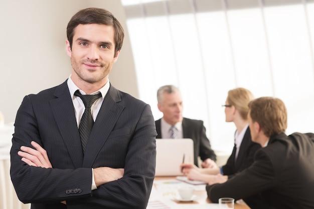 Jest prawdziwym liderem. przystojny młody mężczyzna w stroju formalnym trzymający skrzyżowane ręce i uśmiechnięty, podczas gdy jego koledzy pracują w tle