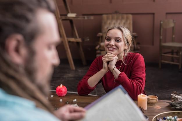 Jest taki mądry. radosna ładna kobieta uśmiecha się, słuchając swojego astrologa