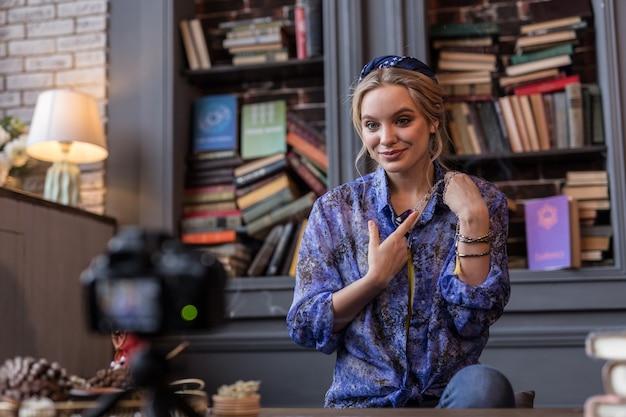 Jest wyjątkowy. zachwycona wesoła kobieta uśmiecha się pokazując piękny talizman do kamery