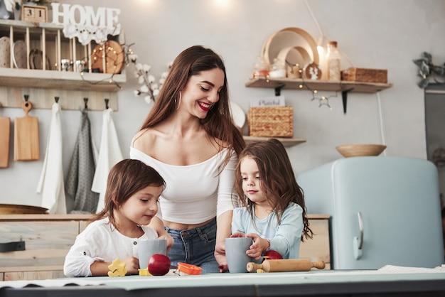 Jest zakochana w tych dzieciach. młoda piękna kobieta daje dzieciom napoje, gdy siedzą przy stole z zabawkami.
