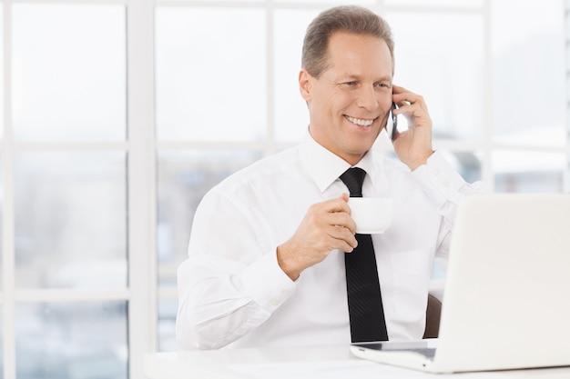 Jest zawsze w kontakcie. wesoły dojrzały mężczyzna w formalwear pije kawę i rozmawia przez telefon komórkowy siedząc w swoim miejscu pracy