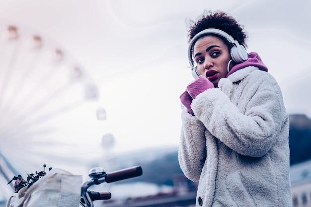 Jest zimno. emocjonalna dziewczyna zaciskająca pięści podczas oddychania na rękach, odwracająca wzrok