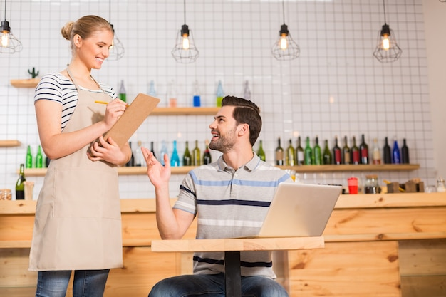 Jestem głodny. szczęśliwy pozytywny zachwycony mężczyzna siedzący przy stole i patrząc na kelnerkę podczas składania zamówienia