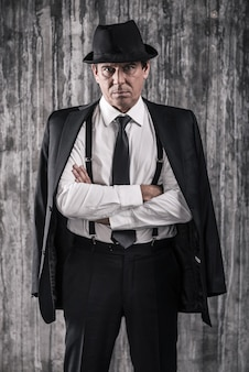 Jestem szefem! apodyktyczny starszy mężczyzna w gangsterskim ubraniu, trzymający skrzyżowane ręce i patrzący w kamerę, stojąc pod ścianą