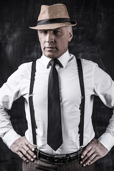 Jestem szefem! pewny siebie starszy mężczyzna w kapeluszu i szelkach, patrząc na kamerę i trzymający się za ręce na biodrze, stojąc na ciemnym tle