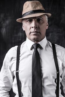 Jestem szefem słyszeć! portret pewny siebie starszy mężczyzna w kapeluszu i szelkach, patrząc na kamerę, stojąc na ciemnym tle