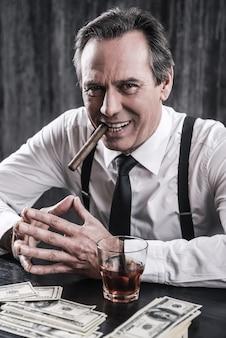 Jestem szefem słyszeć. widok z góry na uśmiechniętego starszego mężczyznę w koszuli i szelkach, siedzącego przy stole i palącego cygaro, podczas gdy obok niego leży mnóstwo pieniędzy
