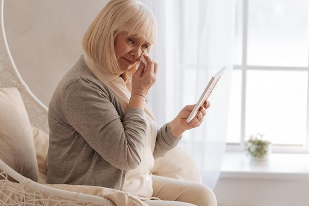 Jestem taki nieszczęśliwy. przygnębiona smutna starsza kobieta oglądająca zdjęcie swojego zmarłego męża i płacząca ocierając łzy