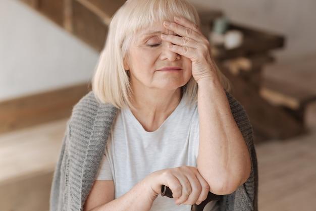 Jestem taki wyczerpany. smutna, miła starsza kobieta zamykająca oczy i dotykająca czoła czując się zmęczona