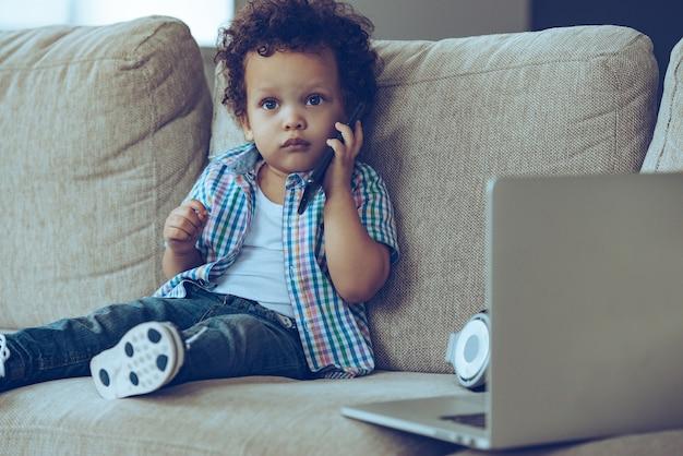 Jestem taki zajęty! mały afrykański chłopiec rozmawia przez telefon komórkowy i patrząc na kamerę, siedząc na kanapie w domu