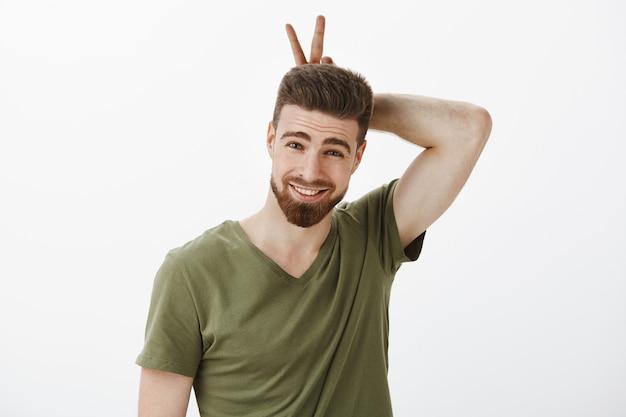 Jestem twoim króliczkiem, kochanie. portret bezczelnego i uroczego romantycznego chłopaka bawiącego się w figlarnym nastroju, pokazującego uszy lub znak zwycięstwa na głowie, małpujący i uśmiechający się uroczo na białej ścianie