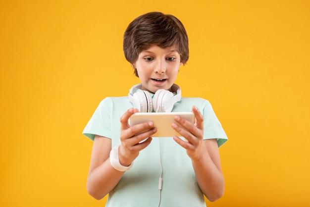 Jestem zainspirowany. podekscytowany ciemnowłosy uczeń korzystający z telefonu i noszący słuchawki
