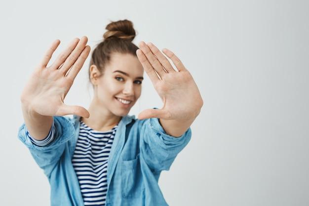 Jesteś bardzo fotogeniczny. studio ujęć kreatywnej pięknej fotografki z fryzurą kok, przyciągającą dłonie do aparatu, mierzącą kąt strzału, szeroko uśmiechającą się i będącą w dobrym nastroju
