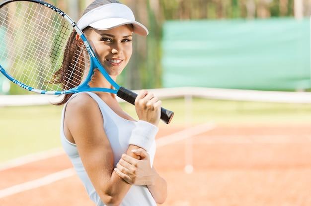 Jesteś gotowy do gry? widok z boku pięknej młodej kobiety w odzieży sportowej, trzymającej rakietę tenisową i uśmiechniętej