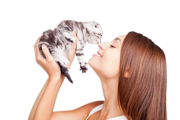 Jesteś moim małym futrzanym przyjacielem! piękna młoda kobieta trzyma małego kotka w rękach i przywiązuje się do niego, stojąc na białym tle na białym tle